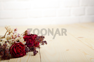 Bouquet of dry flowers and roses on wooden table. Place for text. Brick wall at background
