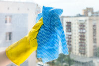 hand cleans glass of home window in urban house