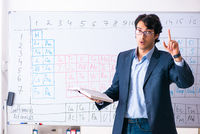 Young male chemistry teacher in front of periodic table