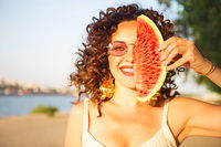 Beauty smiling curly woman is wearing pink sunglasses and eating watermelon