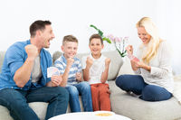 Happy family playing card game on living room sofa at home and having fun together celebrating the game winner