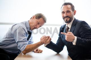 Two businessmen doing arm wrestling in office