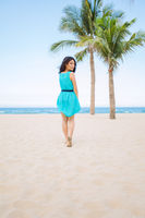 Young beautiful asian woman is walking on the tropical sea beach