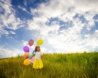 Girl with ballons against blue sky