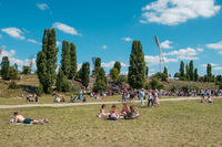 People enjoying sunny summer day on meadow in crowded Park (Mauerpark)  in Berlin City