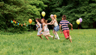 happy kids playing tag game at birthday party