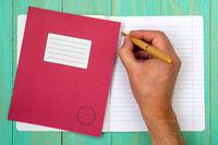 Hand writing in open school notebook
