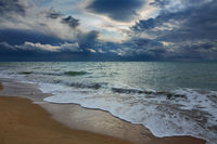 stormy sky over sea and sandy beach