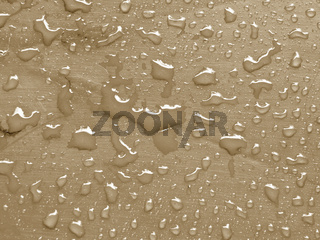 water drops on almond buff colored metallic surface