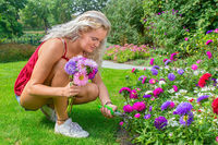 Young woman cuts off summer flowers in garden