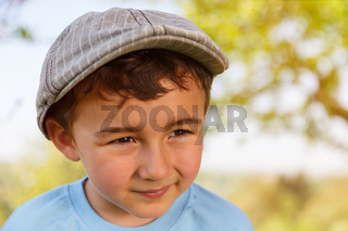 Kind kleiner Junge Textfreiraum Copyspace schaut zur Seite Portrait mit Mütze draußen