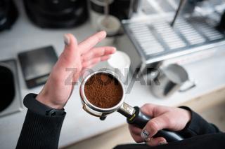 Barista holding portafilter with ground coffee