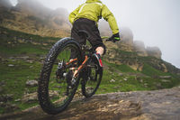 Legs of bicyclist and rear wheel close-up view of back mtb bike in mountains against background of rocks in foggy weather. The concept of extreme sports