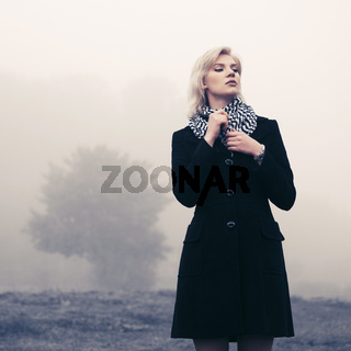 Young fashion woman in black classic coat walking in a fog outdoors