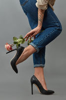 Legs of a girl in classic black high-heeled shoes and jeans near a female hand holding an elegant pink flower around a dark background with copy space. Stylish composition