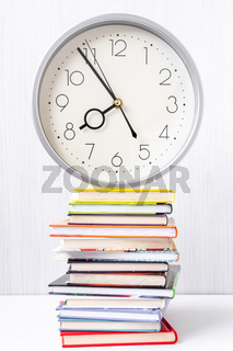 Wall clock and stack of books