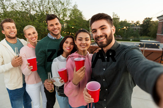 friends with drinks taking selfie at rooftop party