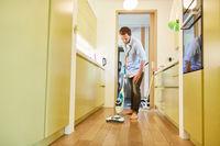 Hausmann reinigt Parkett Fußboden im Korridor