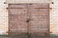 Wooden garage door on brick wall