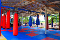 Muay Thai gym with boxing bags and colorful rubber floor at Ban Bung Sam Phan Nok, Phetchabun, Thailand.