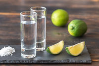 Glasses of tequila with lime wedges