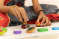 Focus on hands of cute little child girl playing with Indian wooden channapatna toys in the room
