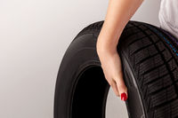 Woman hand holding car tire.