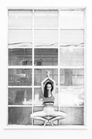 Fit sporty active girl in fashion sportswear doing yoga fitness exercise in front of big industrial window frame. colorful reflections in window glass. Urban style yoga. Black and white