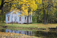 old blue ruined house by the river in autumn park with bright foliage