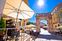 Street of Pula with historic Roman Golden gate and James Joyce statue view