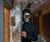 Halloween theme of man with skull mask welcoming you to prison