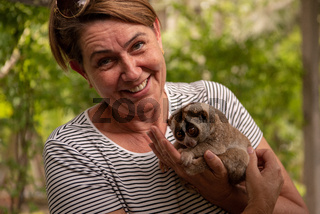 Woman holding slow loris smiles at camera