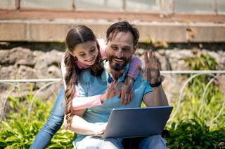 Father with daughter with laptop in park