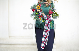 Woman holding Christmas wreath maked by herself