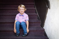 Cute Young Caucasian Boy Portrait Sitting On Stair Steps