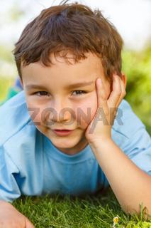 Kind kleiner Junge nachdenken denken schauen Wiese draußen Hochformat