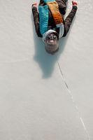 happy woman lying on ice and having fun on frozen lake