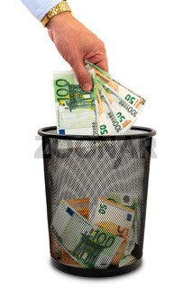 Throwing money away into the trash