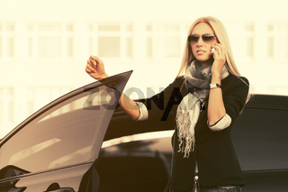 Fashion business woman in sunglasses talking on cell phone outside a car
