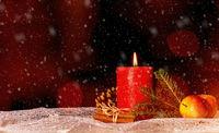 Kerze mit Weihnachtsdekoration und Schnee