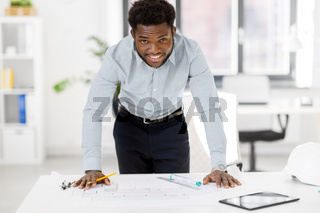 smiling african architect with blueprint at office