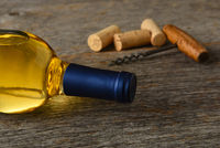 A bottle of Sauvignon Blanc wine with corkscrew and corks on a rustic wood table.