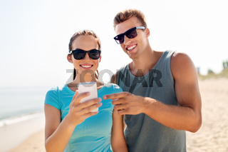 couple in sports clothes with smartphones on beach