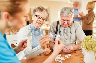 Senioren und Altenpflegerin beim Puzzle spielen