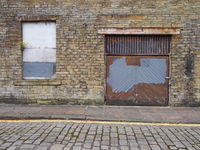 front view of an old abandoned derelict industrial property on an empty street with boarded up window and dilapidated brick walls