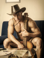 Muscular young man with guitar and cowboy hat