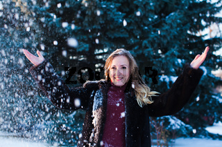 The beautiful woman under the snow in the day