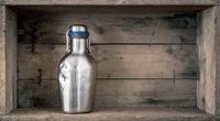 old dented metal bottle on wooden background