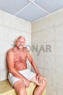Senior Mann sitzt entspannt  in der Therme