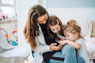 Mom and two daughters are looking at the smartphone